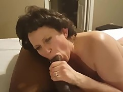 Curly haired mature woman blows big black cock